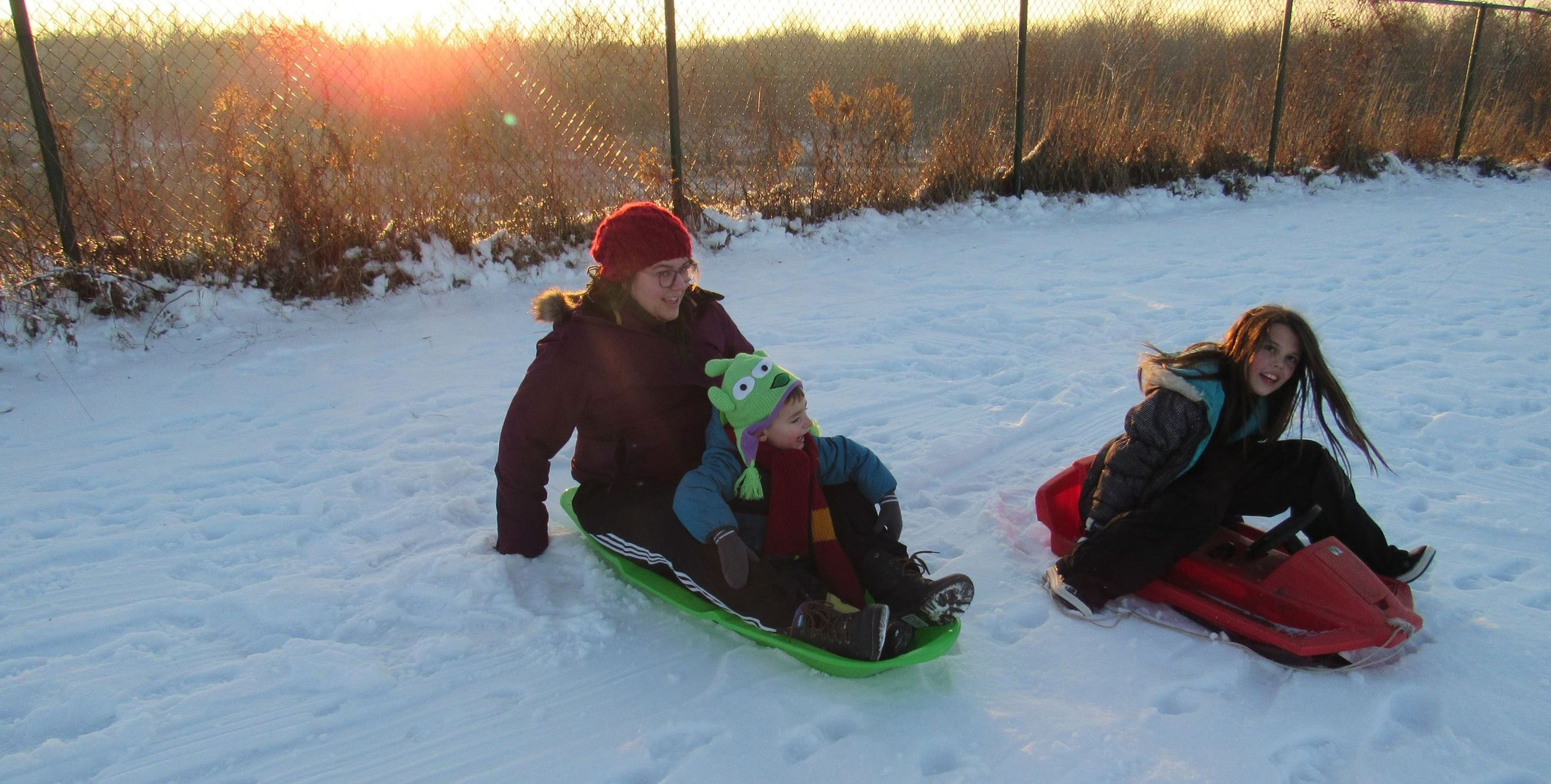 Adult and Child sitting at top of sledding hill in sled.